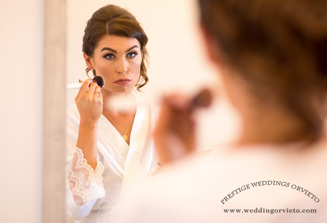 Bride finishing her make up before wear the wedding dress.