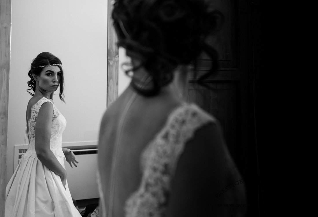white and black photo showing the bride look in the mirror with her dress before to reach the church in Orvieto for her wedding
