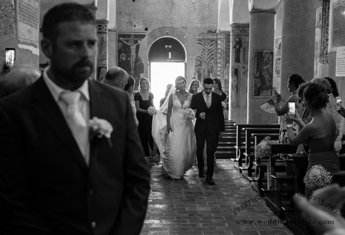 Black and white photo with the bride walking along the aisle to reach her future groom
