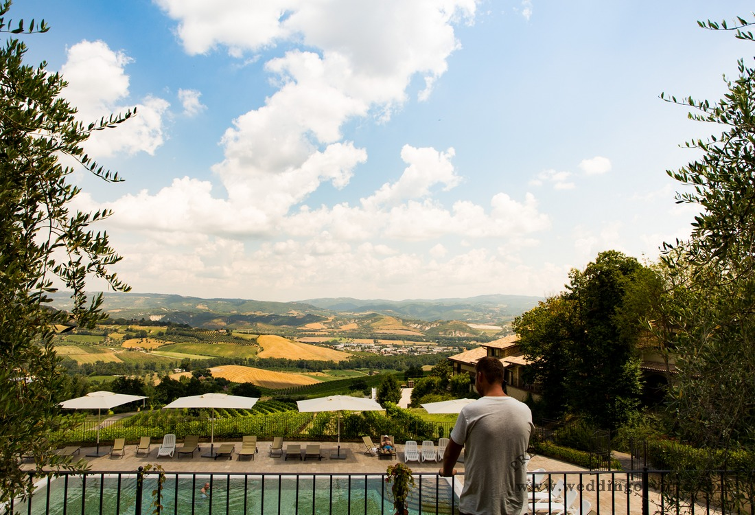 Groom getting ready overlooking hillsides before to go for the ceremony