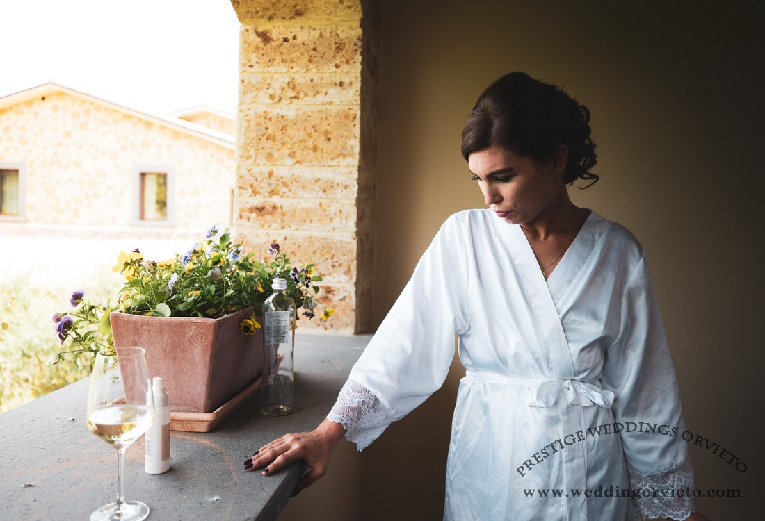 Bride to be on a terrace for getting ready with a glass of white wine