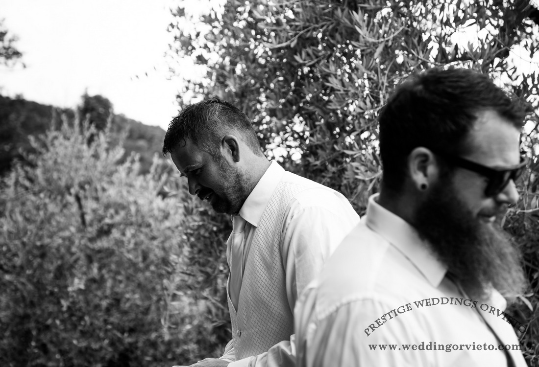 groomsman with long bird and groom together with olive trees in the background white and black photos