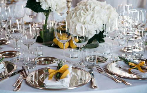Caterer for your wedding in Orvieto. Table cloth white with rosemary and yellow ribbon. Silver charger crystal glasses and the centerpiece including white hydrangea and lemons.