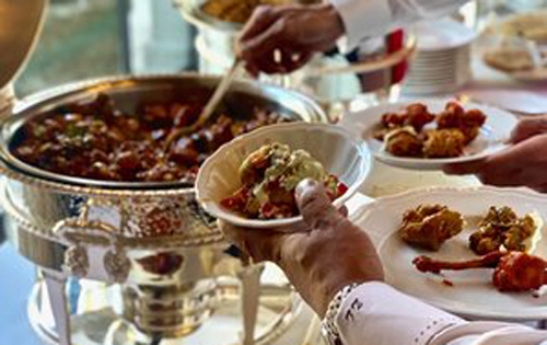 Indian food and caterer for your wedding in Orvieto. People serving food at the buffet.