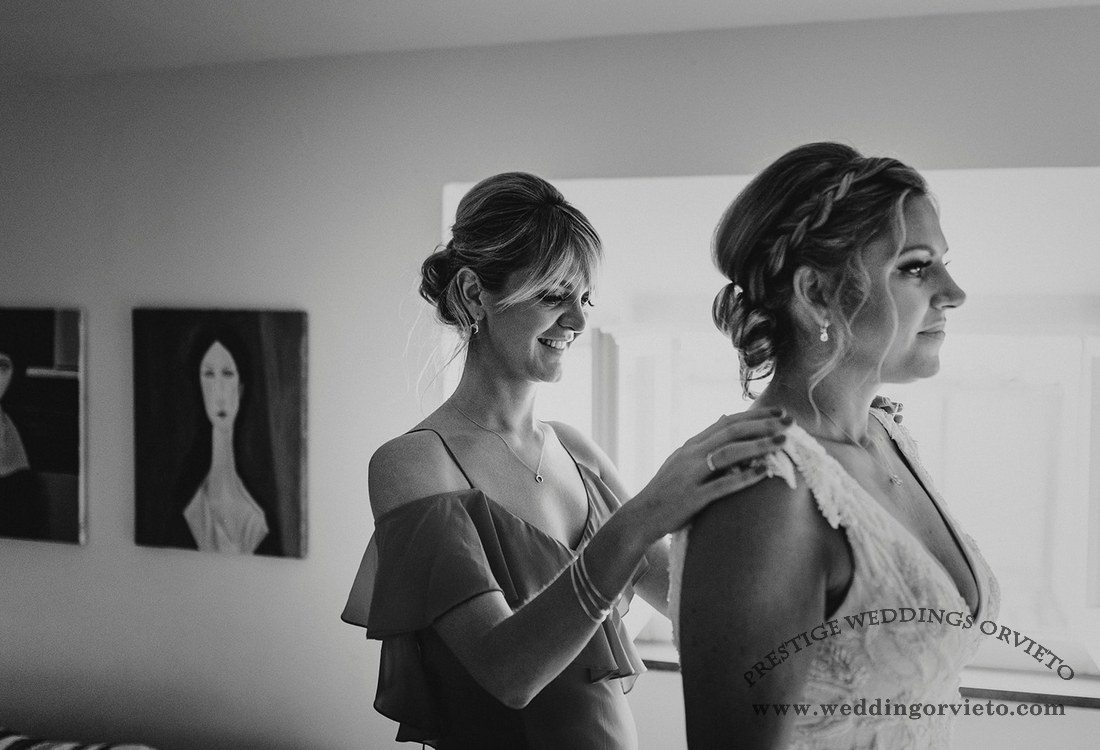 Bridesmaid and bride during getting ready for wedding in Orvieto